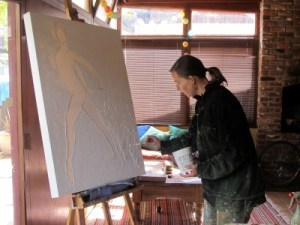 Tana working on a painting of a figure in her home studio.