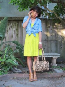 Ready for summer in a knotted and rolled-up denim shirt over a bright yellow bandeau and skirt.
