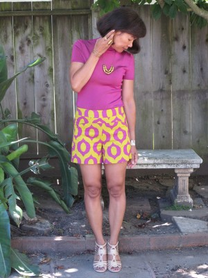 A retro outfit in bright fuchsia and yellow, with brass jewelry and nude strappy sandals.
