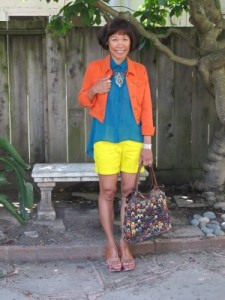 Bright primary crayon colors: denim jacket, flowing asymmetrical hem blouse, and shorts are accessorized with multi-color hobo and printed platform sandals.