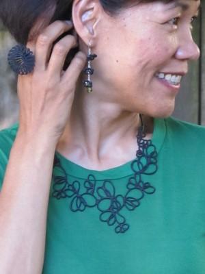 Black accessories pop against a green T-shirt.