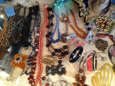 Display case oozing with vintage costume jewelry.
