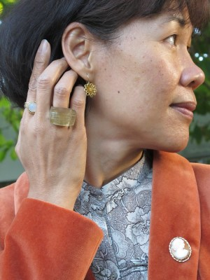 A burnt-orange velveteen jacket is the perfect backdrop for a vintage cameo pin.