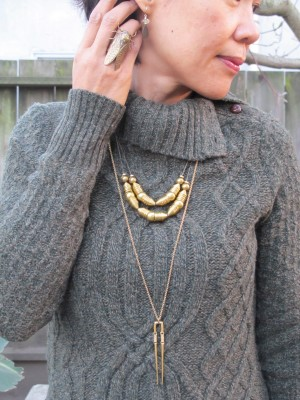 Carmela Rose earrings (Jenny K, El Cerrito), End of Century cicada ring (NYC), Laura Lombardi necklace and longer A Peace Treaty necklace (both, Eskell, Chicago) against a green cabled sweater.