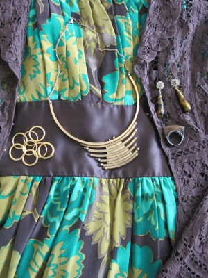 The green, gold, and chocolate flowers and leaves print dress peeks out from an Edwardian-style duster.