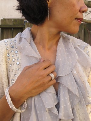 Sheer Swiss dot blouse and cardigan match nicely with Tiffany earrings, ring, and bracelet.