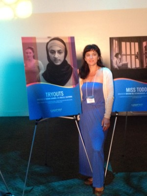 Filmmaker Susana Casares of Los Angeles poses by her film poster for Tryouts.