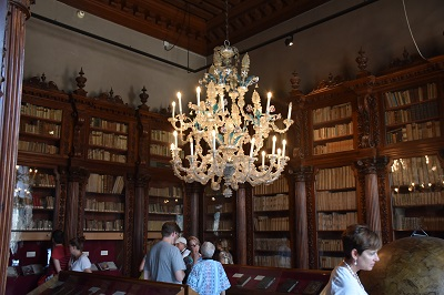 My kind of library - beautiful Venetian glass chandelier, wooden bookcases, and old books.