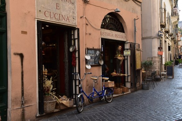 Two-seater bicycle parked between a pizzeria and a kitchen shop.