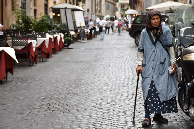 Another street scene, with a gypsy woman walking along the vespas.