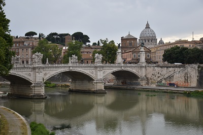 Walking along a bridge over the Tiber River, with another bridge and the Vatican in the background.