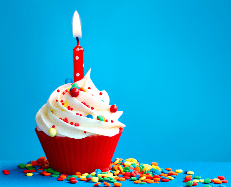 single cupcake with one burning candle on a blue background