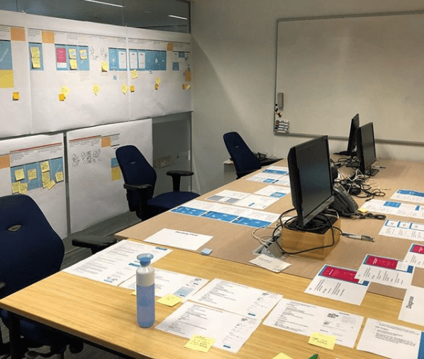 Mock ups of the app and post-its are plastered on the wall and desks
