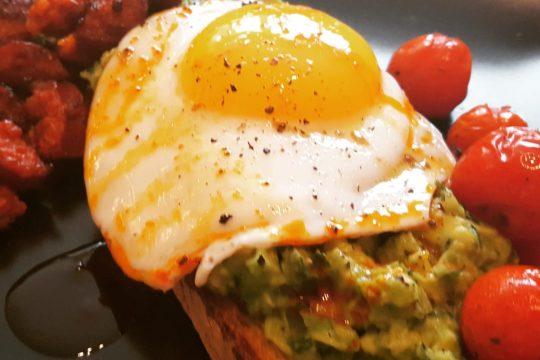 avocado on toast with egg, chorizo and roast tomatoes