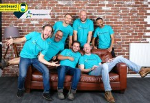 Men posing on sofa against brick wall