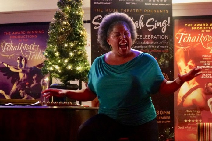 Andrea Baker sings beside piano and Christmas tree