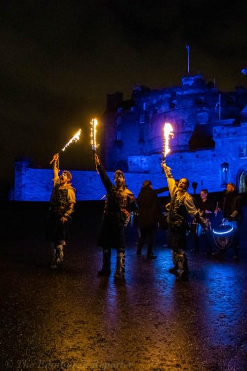 Three men with fiery swords in front of blue castle