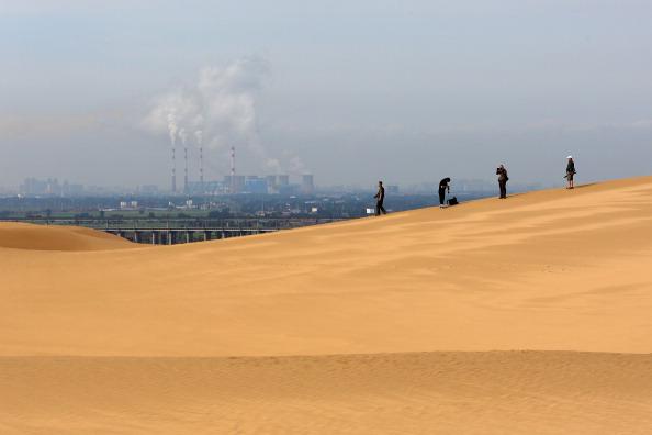 Toursits anda nas dunas perto de uma central energética no deserto de Xiangshawan em Ordos de Inner Mongolia, nesta foto do arquivo. Os mineradores de bitcoin desfrutam de taxas de eletricidade favoráveis em lugares como Ordos há muito tempo (Feng Li / Getty Images)