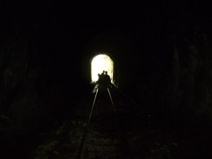 Tunnel all in darkness with a small opening at the end showing the silhouettes of several people
