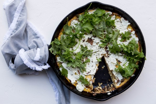 Frittata in a cast iron skillet covered in goat cheese and sprinkled with arugula