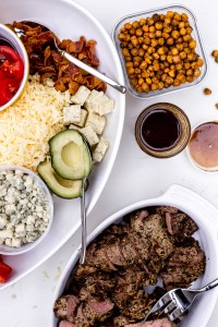 A dish of salad toppings next to a container of dressing, a dish of cooked and sliced steak, and a container of roasted chickpeas that have spilled out of their container.