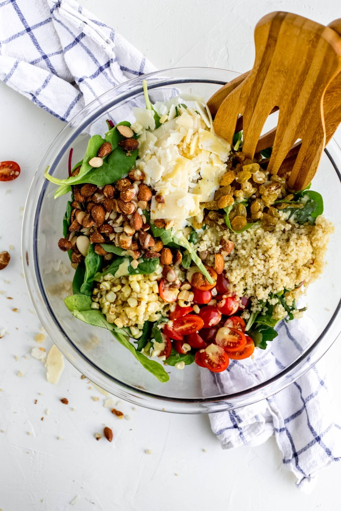Smoked Almond and Corn Quinoa Salad in a clear mixing bowl with large salad serving tongs beside some spilled ingredients.