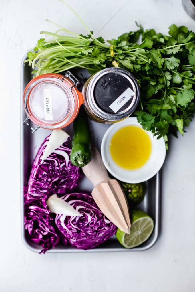 A baking sheet with all the ingredients for mexican slaw - cabbage, lime, a wooden lime juicer, olive oil in a dish, a jar of cumin, a jar of salt, and a bunch of cilantro.