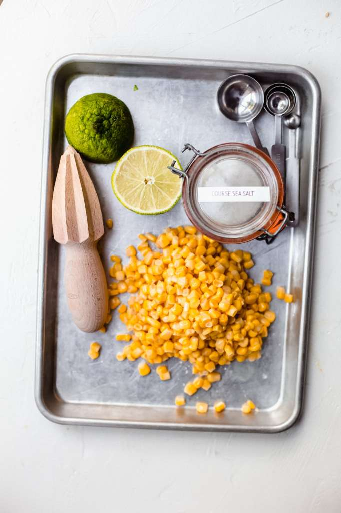 A sheet pan with a pile of canned corn, a citrus reamer, a halved lime, a jar of salt and some measuring spoons.