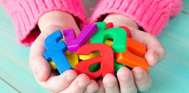 A girl holding magnetic letters