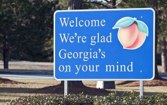 """A welcome sign with a picture of a peach and the words """"Welcome, we're glad Georgia's on your mind"""""""