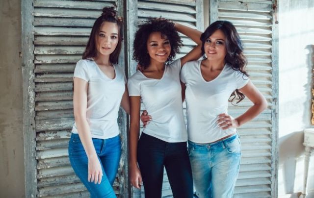 Three young women wearing white t-shirts