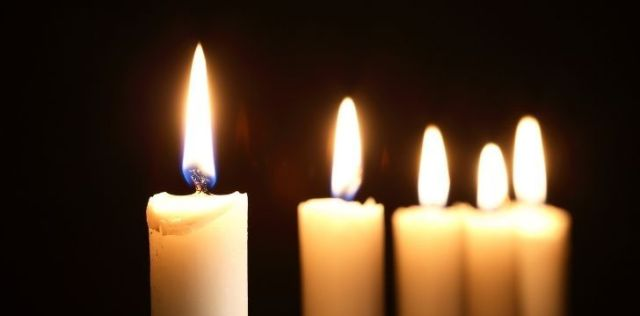5 simple tall white candles lit in the dark
