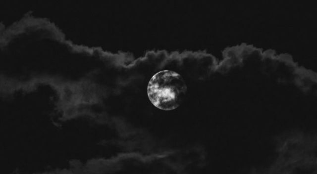 A full white moon in a dark sky with clouds