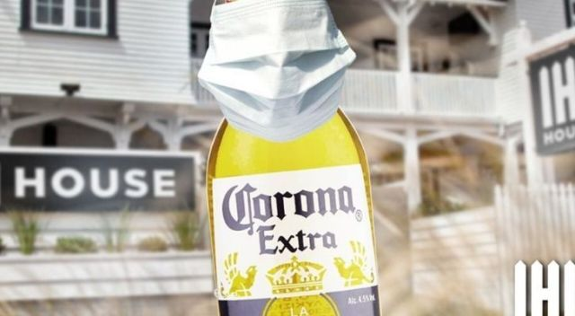 A Corona beer bottle being socially responsible wearing a face mask