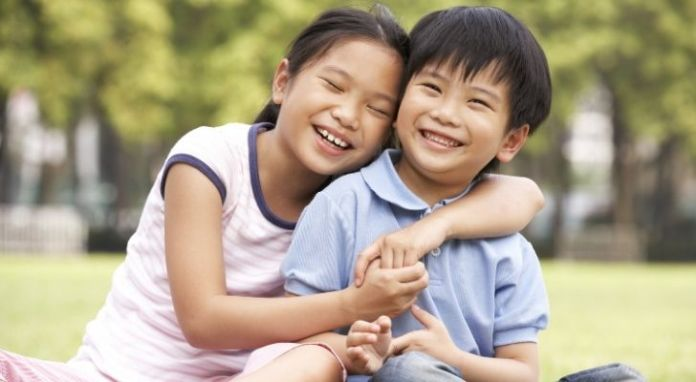 A Chinese brother and sister smiling