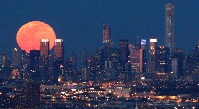 A pink superman shining above a city skyline
