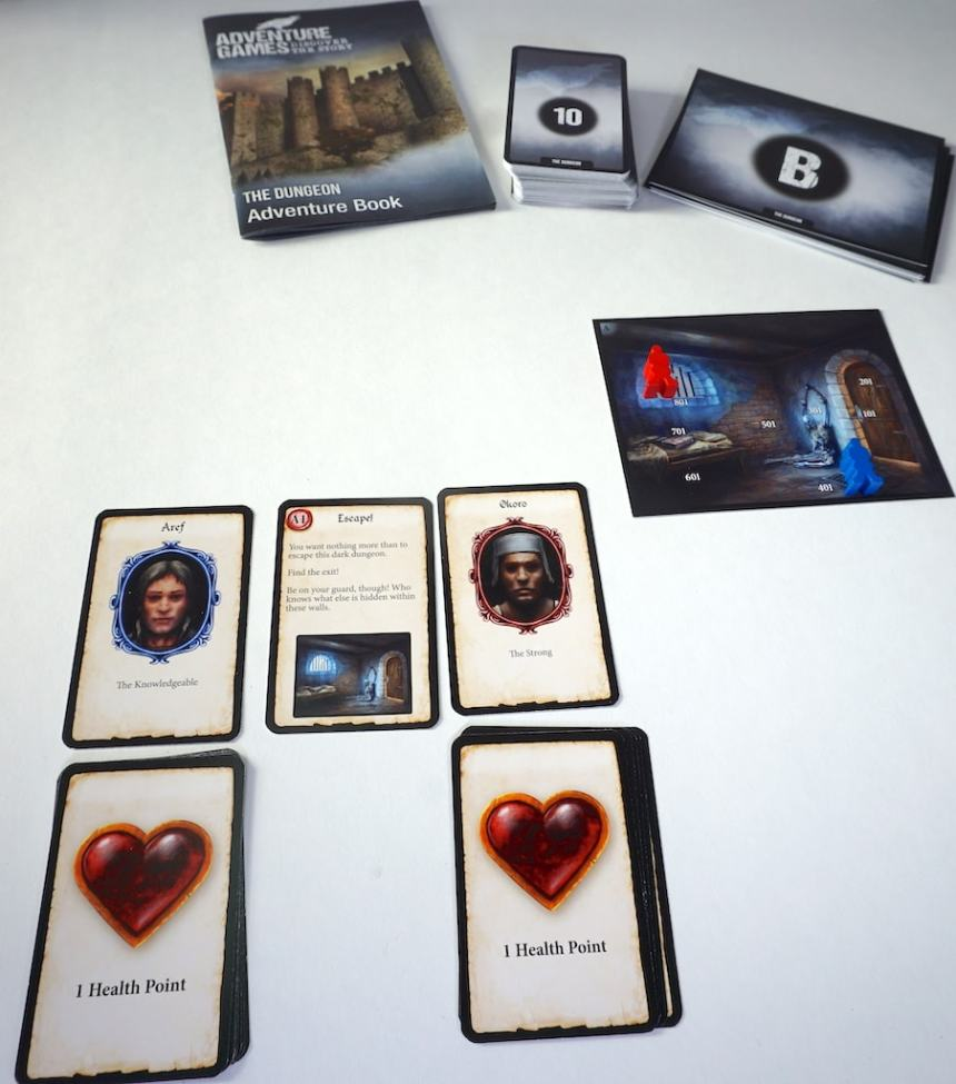 """Adventure Games: The Dungeon Adventure Book. Deck of cards showing a """"10"""". Deck of large room cards showing a """"B"""". Room card A is visible and pictures a dungeon cell. Character cards """"Aref"""" and """"Okoro"""" are visible with stacks of heart cards beneath them."""