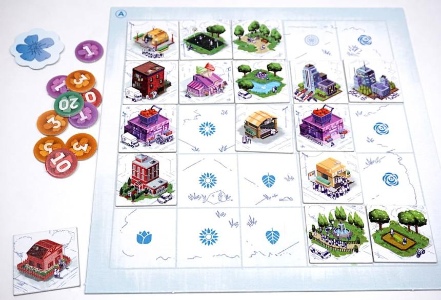 A town board with shops, parks, offices, and residences. A pile of point tokens is off to the left.