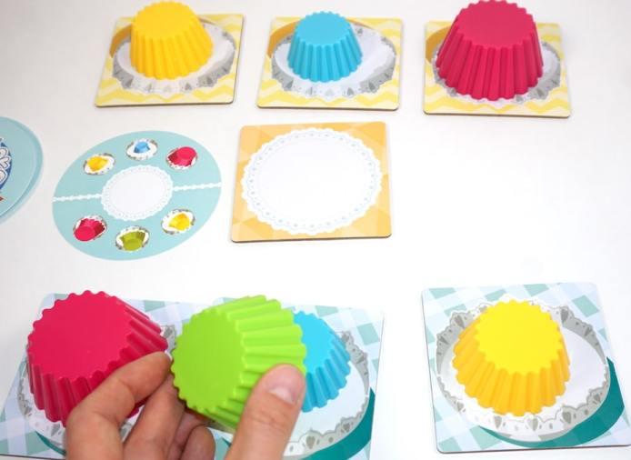 Hand lifting a green cupcake liner