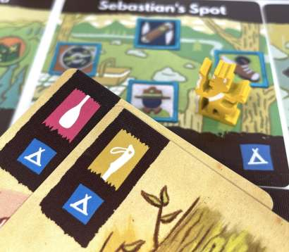Yellow scout meeple on map card Sebastian's Spot - a blue square tent area. 2 supply cards are shown in foreground, both with blue square tents.