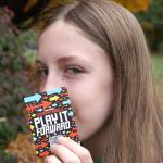 Girl holding a card. Written: Play It Forward