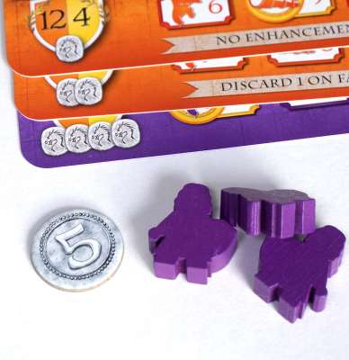 Purple meeples next to a stack of 3 cards, showing 1, 2, and 4 dragonstones. A silver 5-coin is also in the picture.