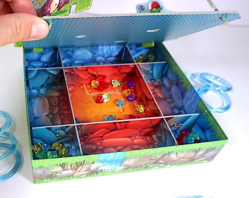 A hand tipping up the Dragon's Breath board to reveal the box underneath. Gems have fallen into 5 divided areas.