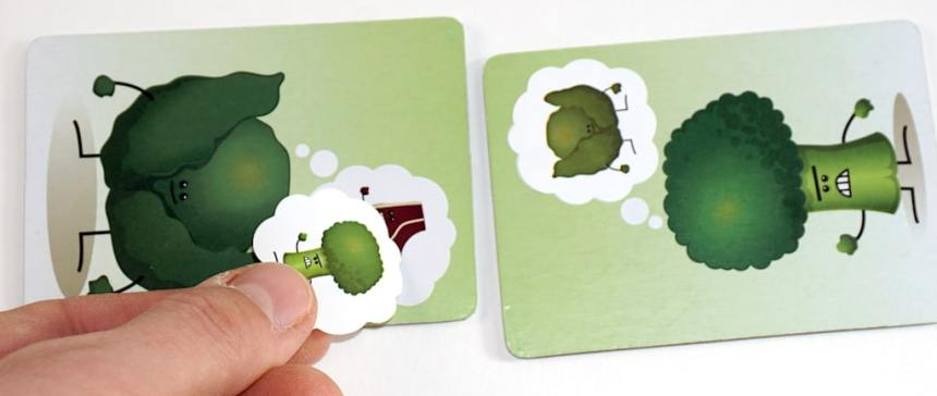 Food Fighters Cabbage tile with fingers placing a broccoli sticker. Broccoli tile with a cabbage thought bubble.