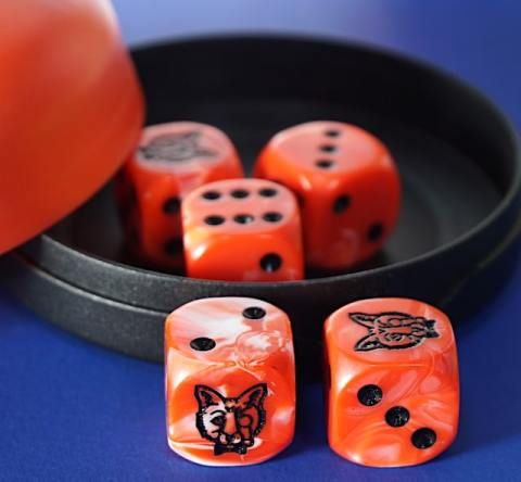 Red dice cup. 2 dice are outside, 3 are inside.