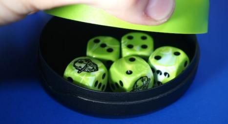 """Green dice cup showing 5 dice: 1 wild """"cheetah"""", 2 twos, 1 three, 1 four"""