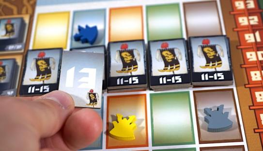 A line of war banner tiles stating 11-15. Fingers holding a flipped tile with the number 13 showing.