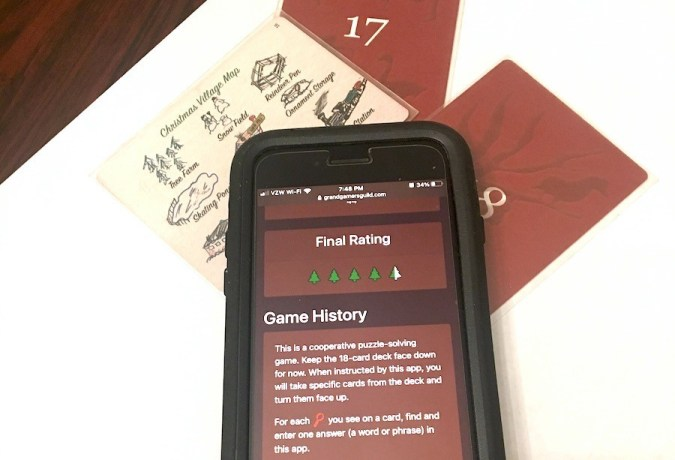 "Cards underneath a cell phone, which says: ""Final Rating 4.5 trees. Game History: This is a cooperative puzzle-solving game. Keep the 18-card deck face down for now..."""