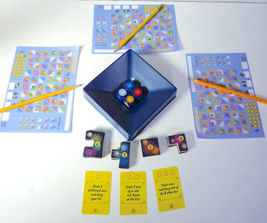 3 player sheets around a central dice tray. Polyomino shapes are on the 4th side of the tray, with 3 cards next to them.