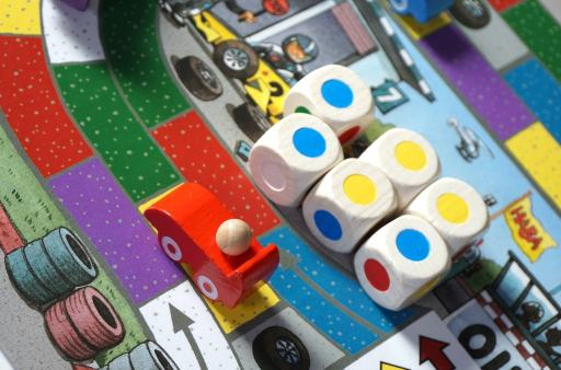 Red car on the racetrack. Six dice all show blue or yellow. Spaces next to the car are purple, green, and red.